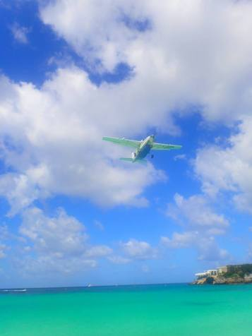 A small plane landing at Maho Beach
